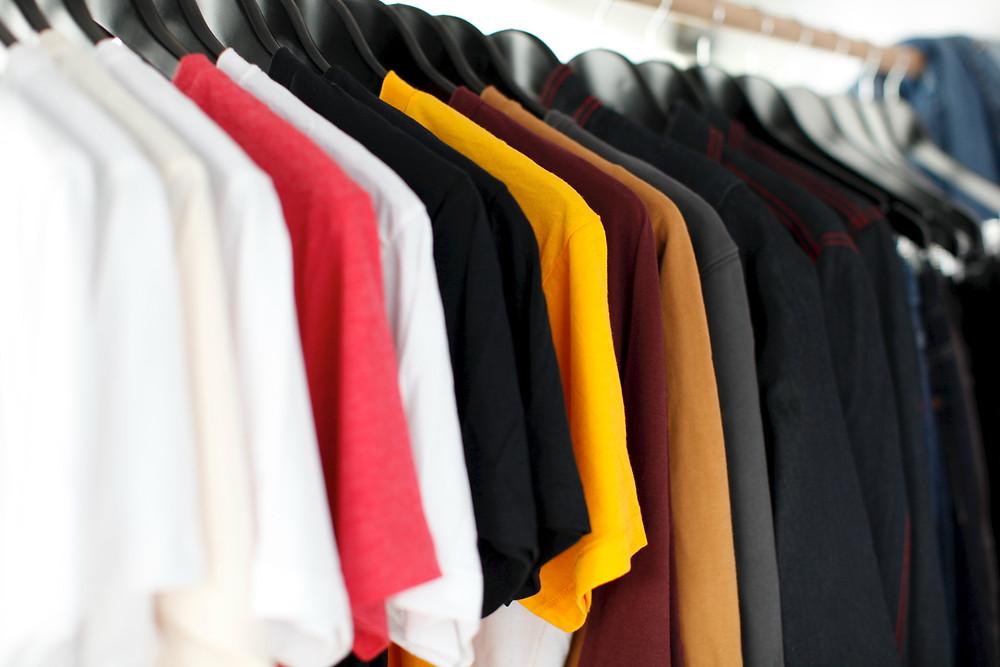 Ряд вешалок с разноцветными футболками