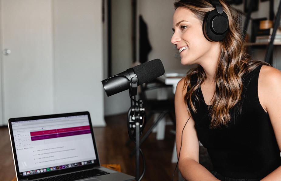 Mujer grabando un podcast con auriculares y micrófono profesional