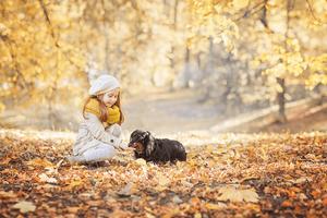 little girl feeding dog on field