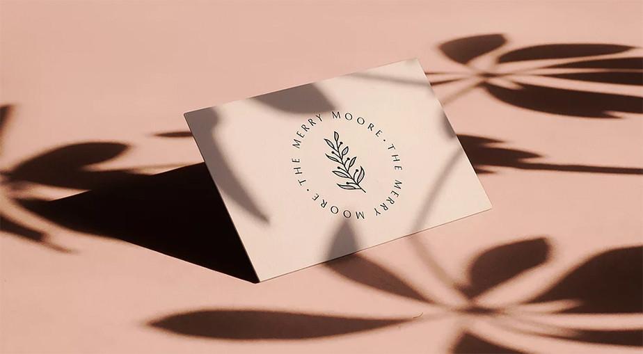 Tarjeta personal rosa con una hoja.