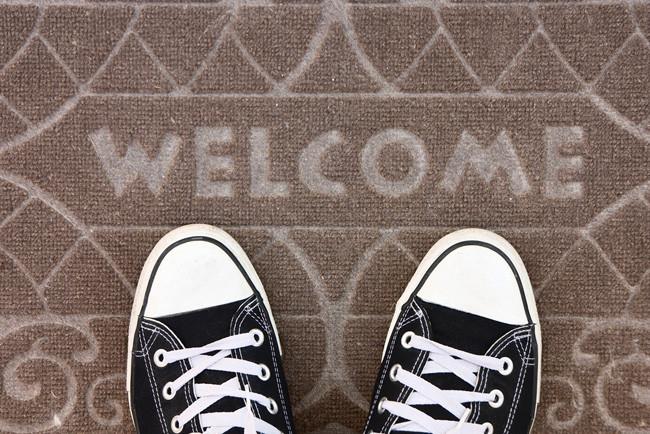 """Кеды над ковриком с надписью """"Добро пожаловать"""""""