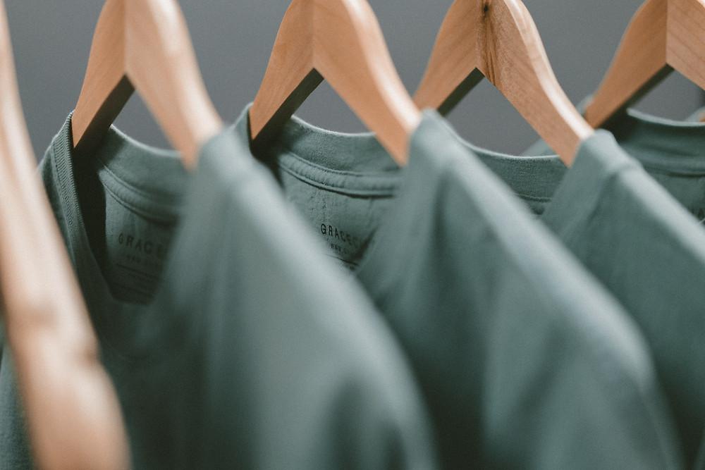 Ряд вешалок с футболками цвета хаки