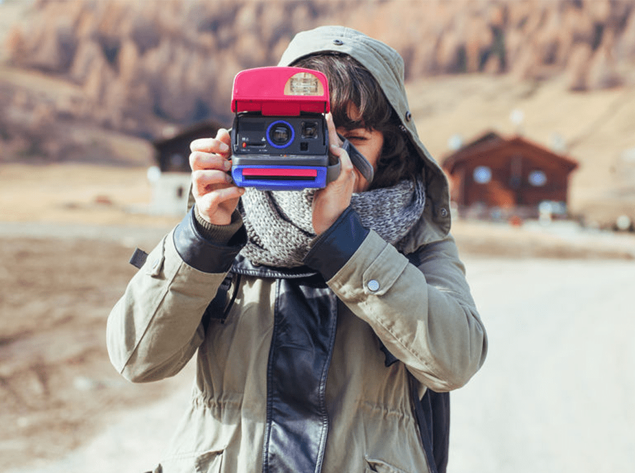 girl holding a polaroid camera