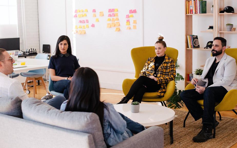 5 pessoas sentadas em uma sala realizando uma reunião informal