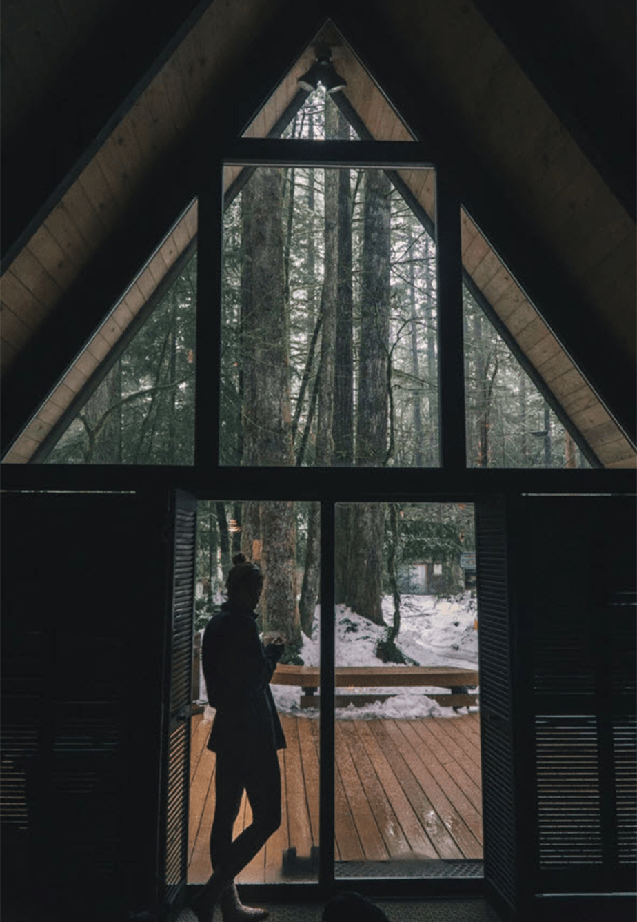 girl standing on cabin in snowed winter forest