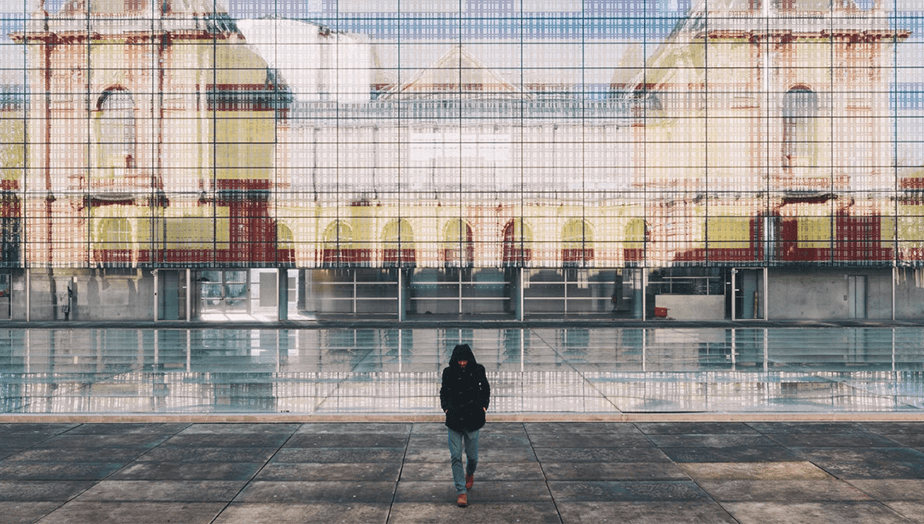 person standing in front of glass building with colored reflection