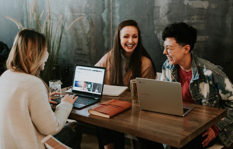 3 pessoas trabalham e conversam em uma mesa com laptops