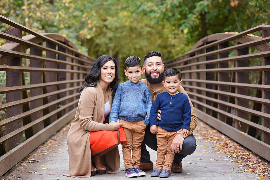 family with matching outfits on forest bridge