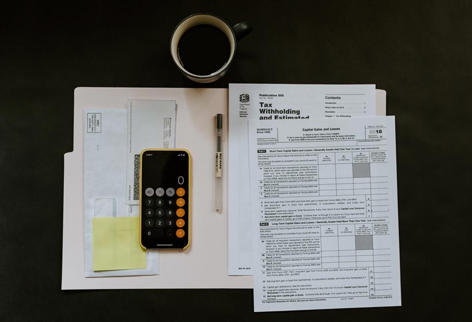 Een afbeelding van belastingpapieren, een kop koffie en een rekenmachine