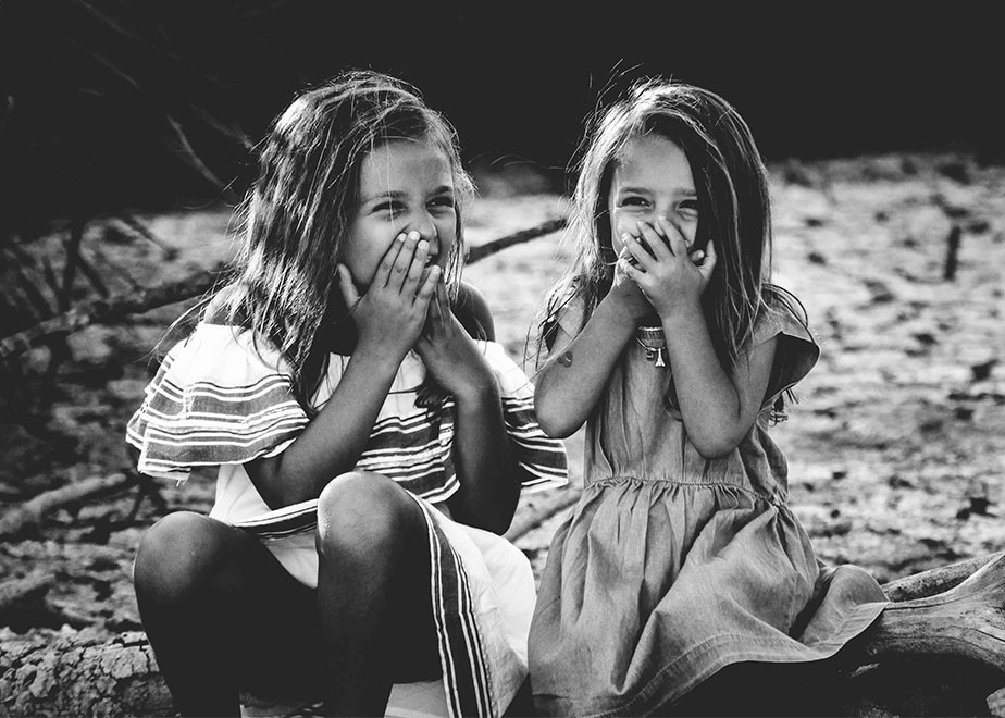 black and white lifestyle photography portrait of two girls laughing
