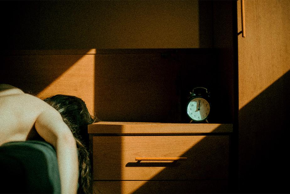 Fotografia we wnętrzu - kobieta leżąca w łóżku obok budzika