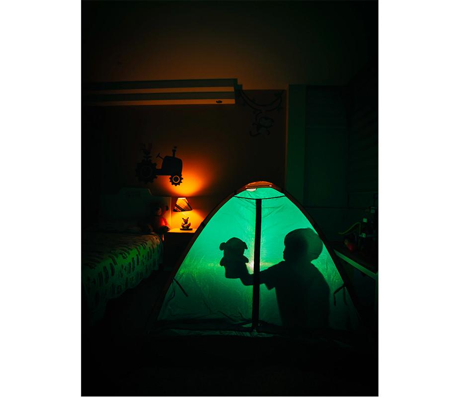 Fotografia wewnętrzna - oświetlenie i cienie dziecko bawiące się w namiocie