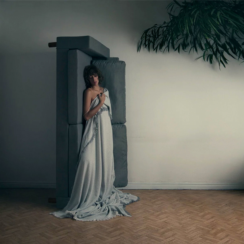 Fotografia wewnętrzna - kobietą opierająca się na pionowej kanapie