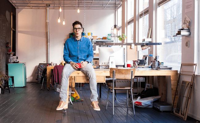 молодой человек сидящий на рабочем столе