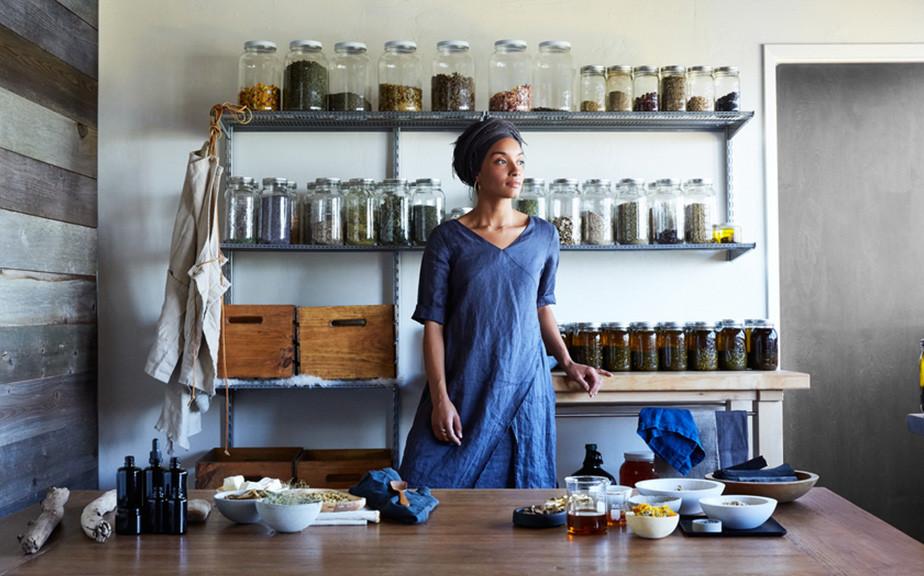 Afbeelding van een bedrijfseigenaar in haar specerijen winkel met grote glazen potten in een rek op de achtergrond.