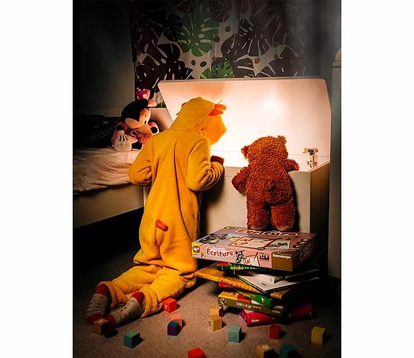Fotografia wnętrz - dziecko i pluszowy miś patrzą wgłąb pudełka z zabawkami