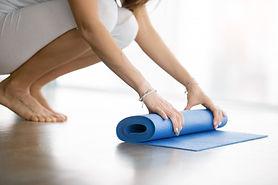 close-up-female-hands-unrolling-yoga-mat
