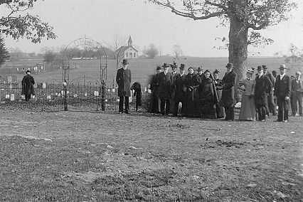 Old picture of church ongregation standing by gate to cemetery