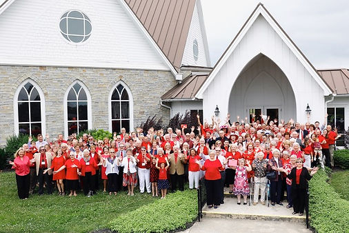 Large group of people wearing read outfits and with their hands in the air in front of Opequon Church