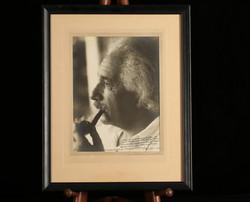 Sepia photograph of Einstein smoking a p