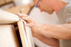 focus on the robust hand of a carpenter placing a flap (a wooden board) on a piece of a handcrafted
