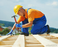 man-on-top-of-roof-wearing-hard-hat-with-hammer.jpg