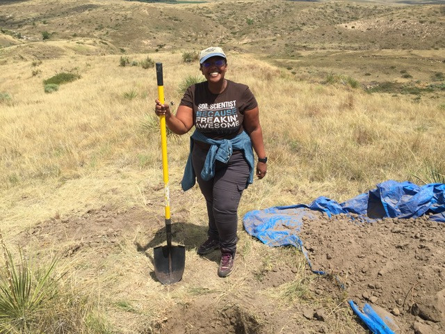 Dr. Asmeret Asefaw Berhe outside in the field holding a shovel.