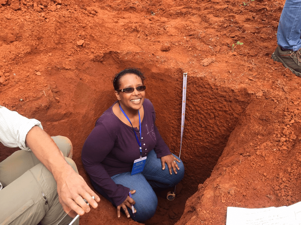 Dr. Asmeret Asefaw Berhe sitting in a soil pit. The soil is bright redish-orange containing soil horizons with minimal differentiation.