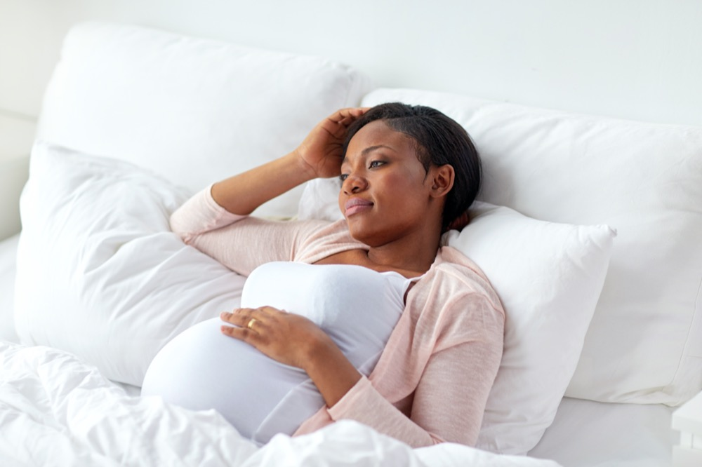 pregnant-woman-lying-in-bed-at-home-PN39