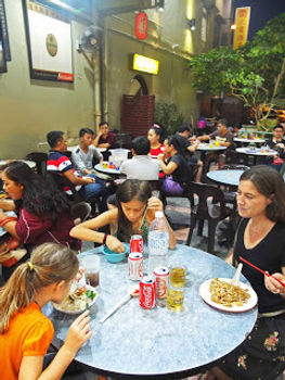 Familytravel: a family eats in a restaurant in Kuching, Borneo