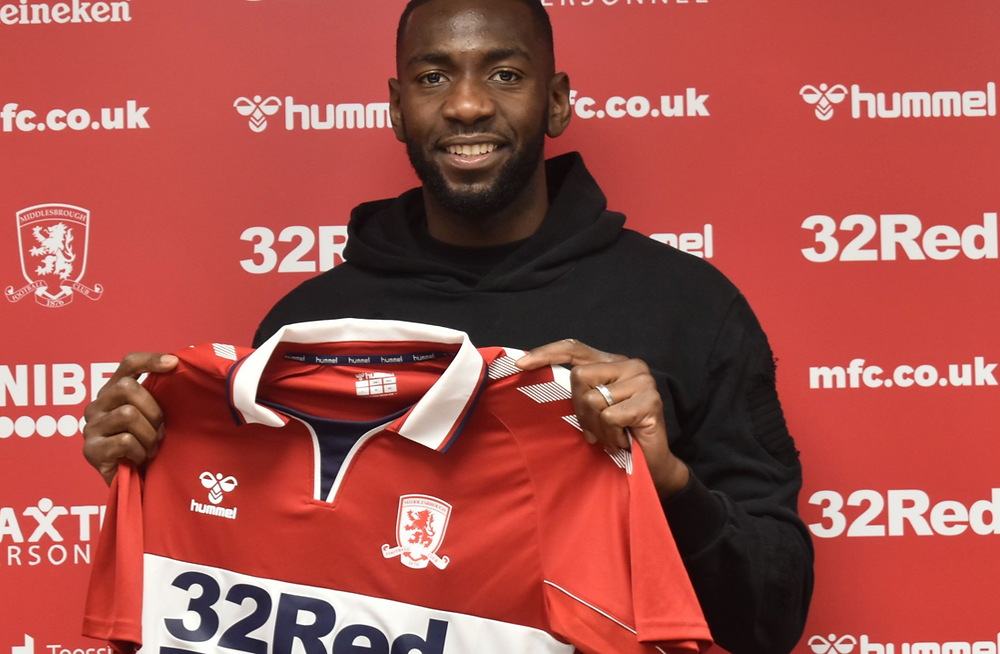 Yannick Bolasie holding 2020/2021 Boro shirt in front of a red sponsor background