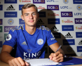 Kiernan Dewsbury-Hall with a contract in front of him and a pen in hand