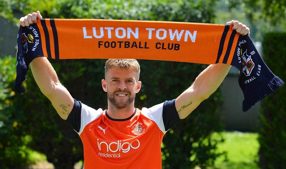 Martin Cranie in a Luton Town kit holding a Luton Town scarf