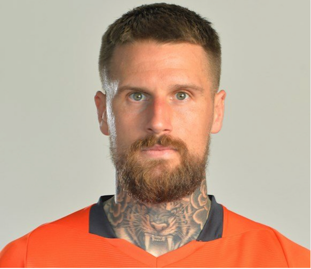 Sonny Bradley staring at the camera wearing a Luton Town home shirt