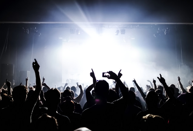 silhouettes of concert crowd in front of bright stage lights.jpg