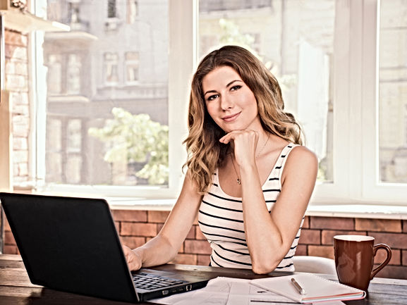 Photo of an Melli At Home Advisor wearing a headset and sitting at a desk with an makeup product.