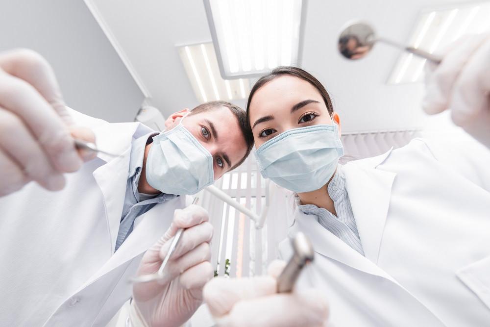 Um dentista homem e uma denitista mulher segurando instrumentos ortodônticos.