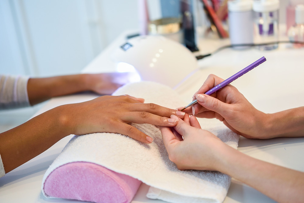 Imagem de uma mão recebendo tratamento por meio de uma manicure