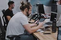 junger Mann im Büro am Schreibtisch mit