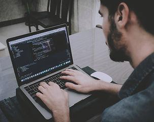 Mann am Laptop mit Code
