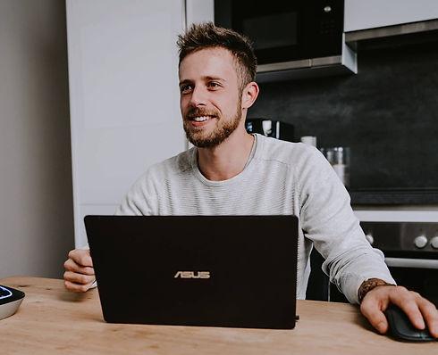 junger Mann lächelnd am Laptop in einer