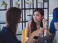 2 junge Frauen unterhalten sich am Arbei