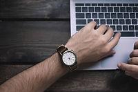 Männerarm mit Uhr und am Laptop