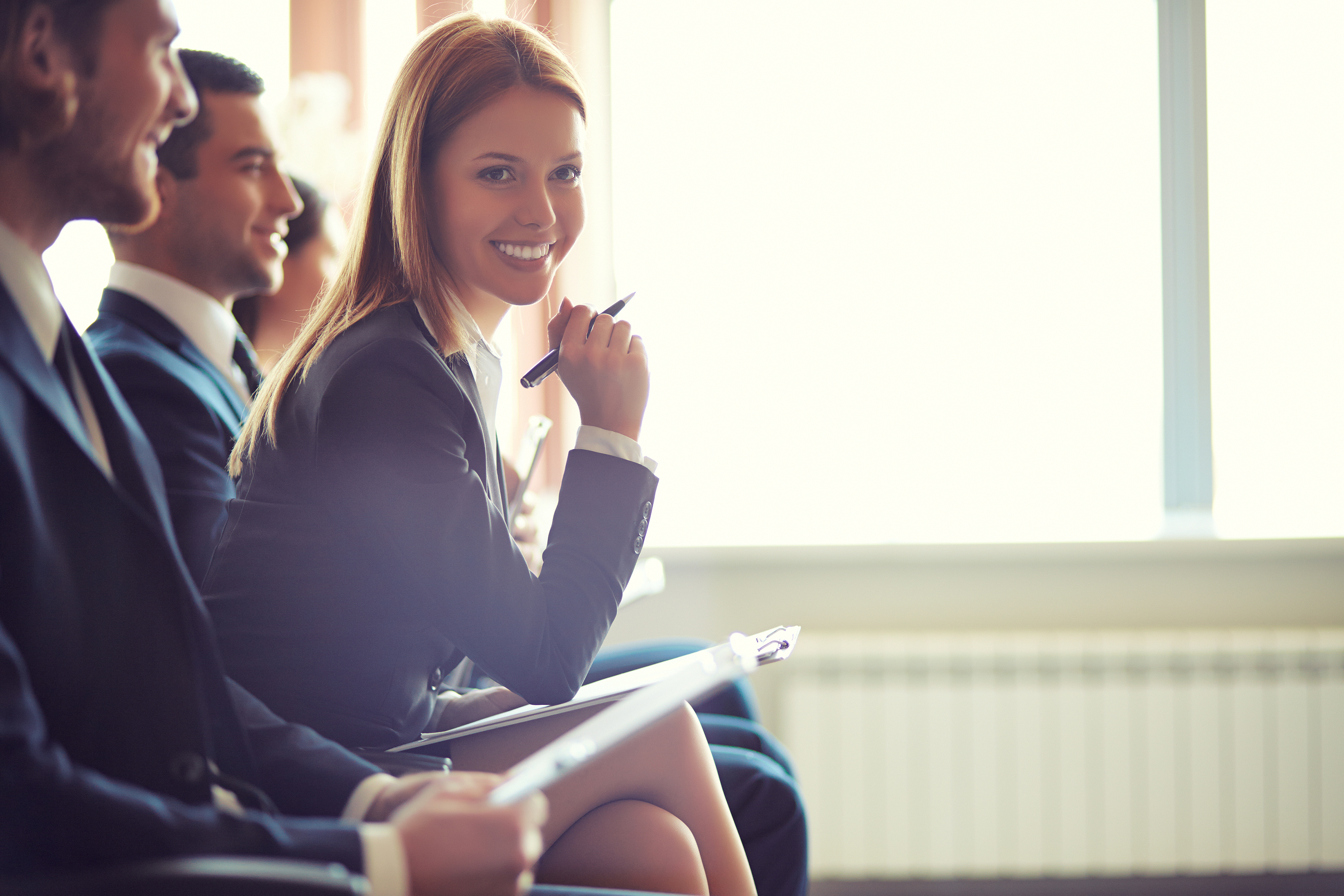 Row of business people sitting at seminar, focus on attentive young female.jpg