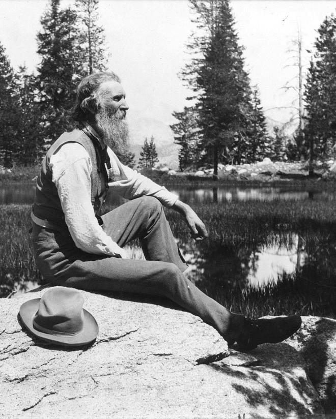 John Muir, circa 1902, sitting by a lake