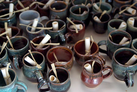 Several stoneware mugs - glazed in dark red, green, and brown - with a rolled up note in each mug.
