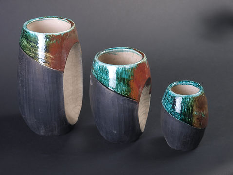 A set of three nesting vases, tallest on the left and shortest on the right. All have black matte body and iridescent green and rust colored glaze at the top. Largest two have concave white sections where smaller vase can nest.