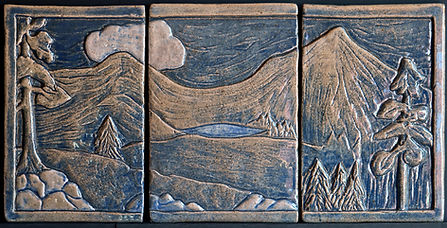 A carved tile triptych, with an image of mountains, trees, and a lake. All glazed in blue.