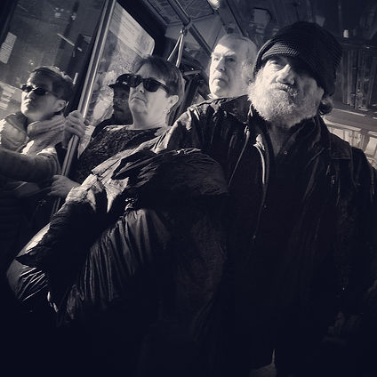 A black and white photo of people standing on a bus. An older man with a big white beard and a black cap, black jacket stands in front of the group. Another man with white hair, and a woman wearing sunglasses stand behind him. All of them have a serious look on their faces.