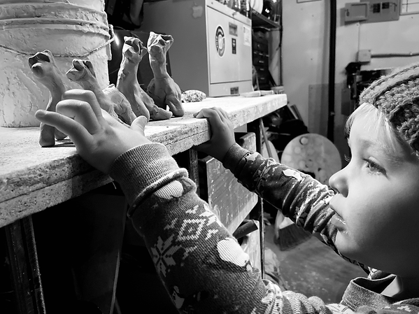 Black and white image of a little boy looking up at four small clay llamas lined up on a workbench in an art studio.